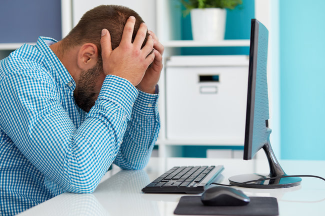 Young business man under stress with headache